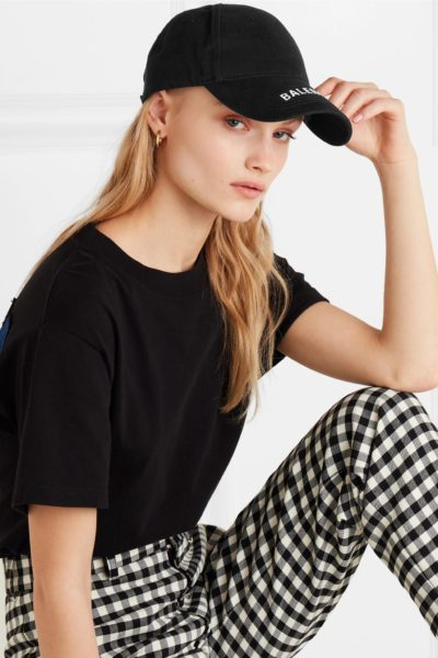 Trendy designer baseball caps featured by top US fashion blog, A Few Goody Gumdrops: image of a woman wearing a Balenciaga baseball cap